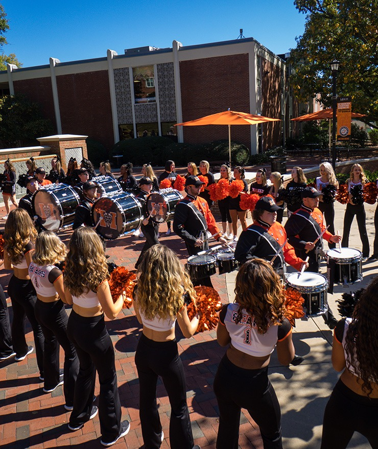 Mercer cheerleaders and Mercer dance team members cheer as Mercer band drummers play on campus during Homecoming 2018 festivities in Macon.