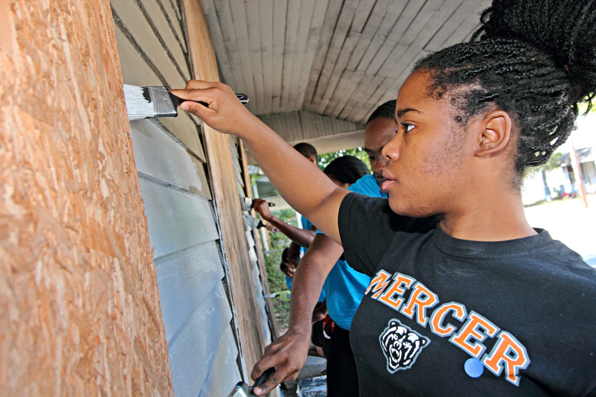 A Mercer University student paints a house.