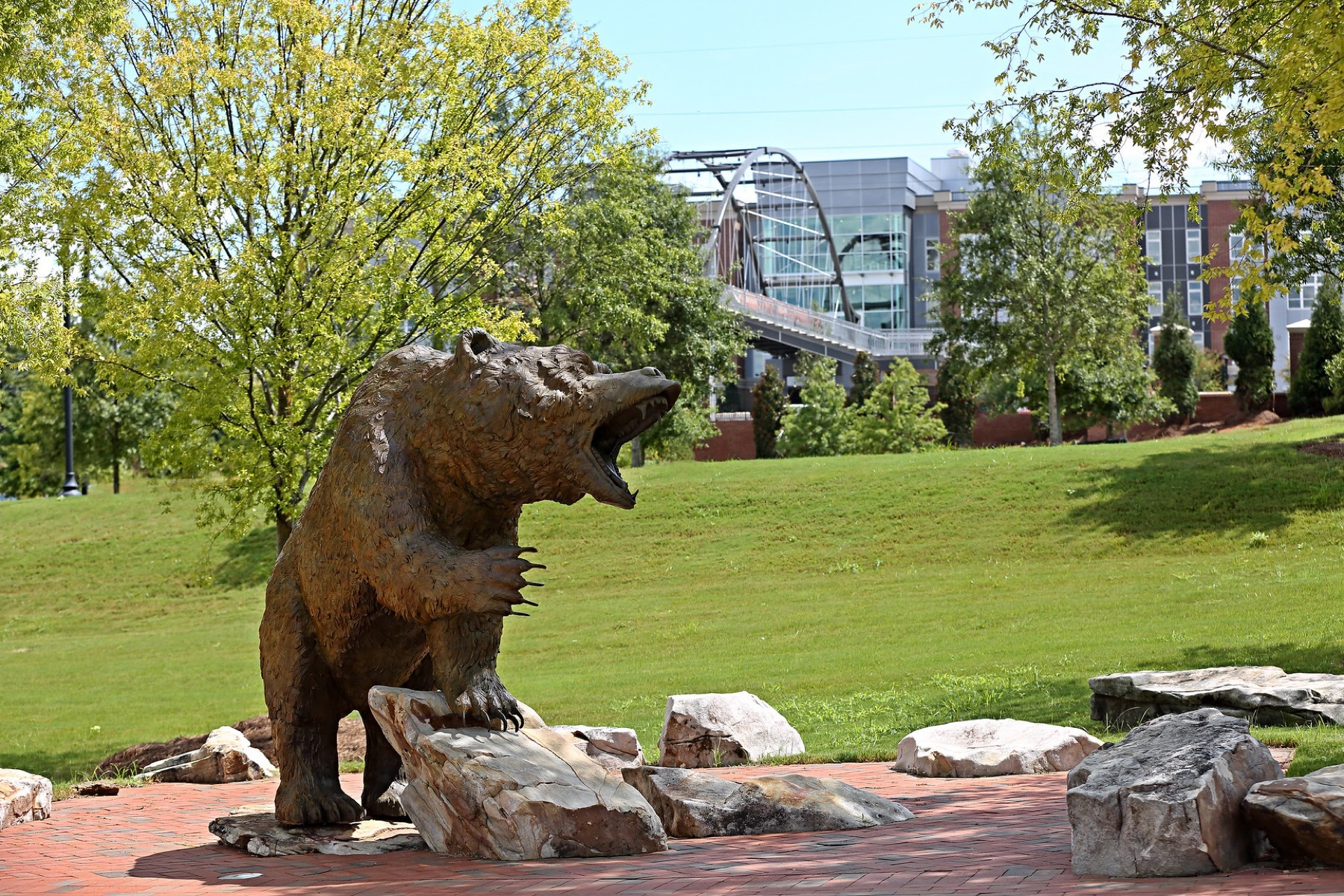 A bear statue is pictured, with the Lofts at Mercer Landing and pedestrian bridge in the background.