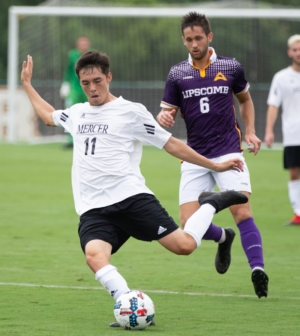 Men's soccer player Roberto Arteaga kicks the ball.