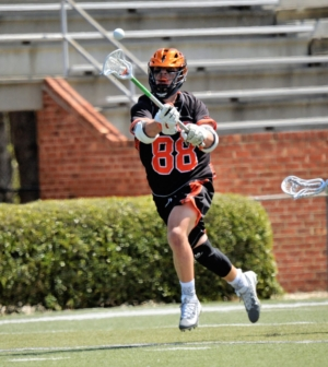 Men's lacrosse player Ashton Wood runs down the field.