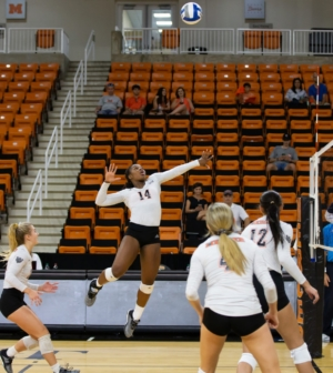 Women's volleyball player Brittany Major spikes the ball.