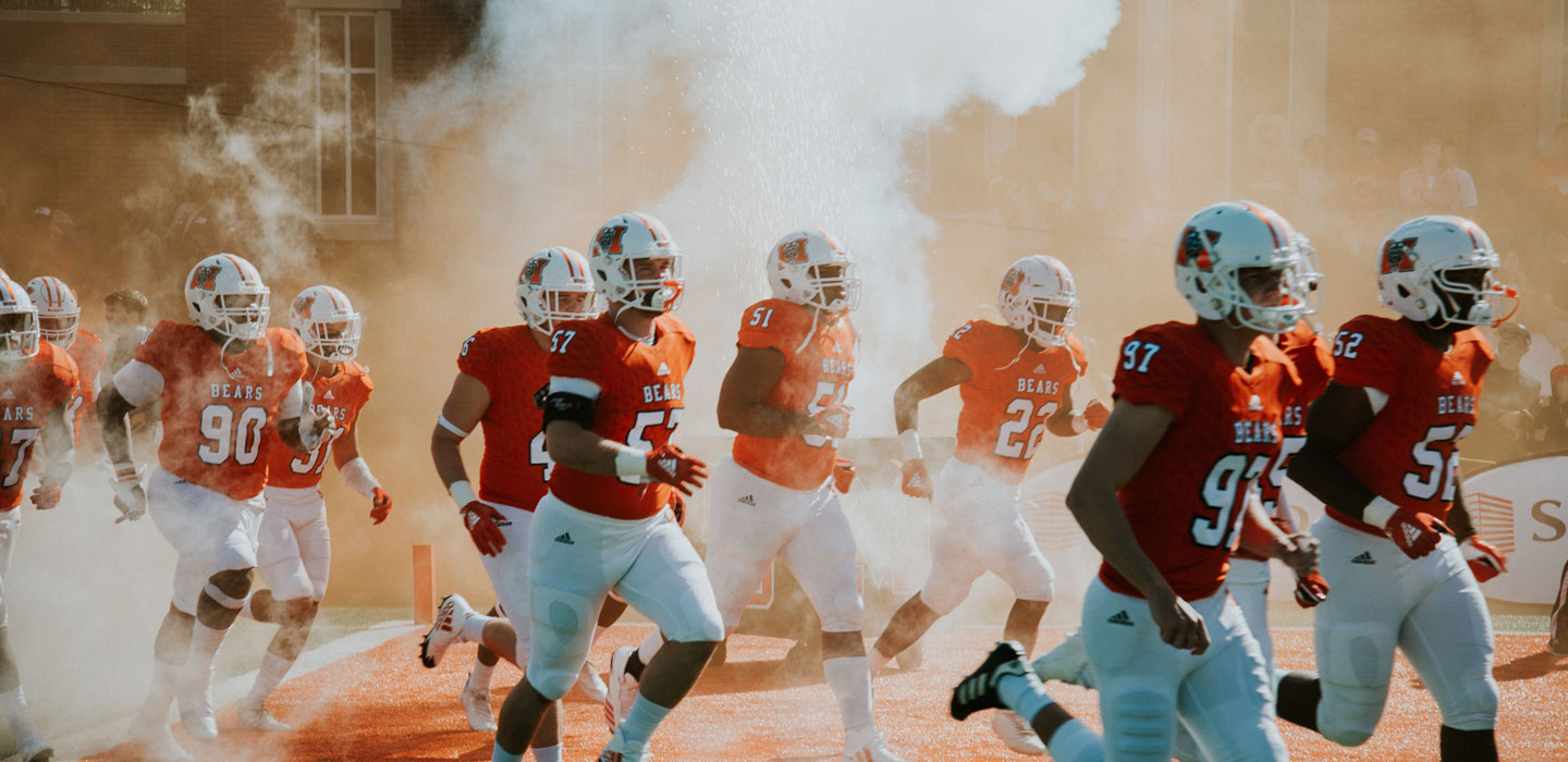 Football players rush the field in orange jerseys
