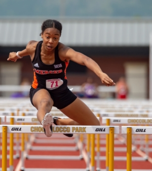 Women's track and field team member Cherrish Wright clears a hurdle.