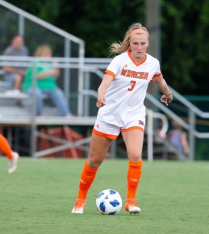 Women's soccer player Abigail Zoeller kicks the ball.
