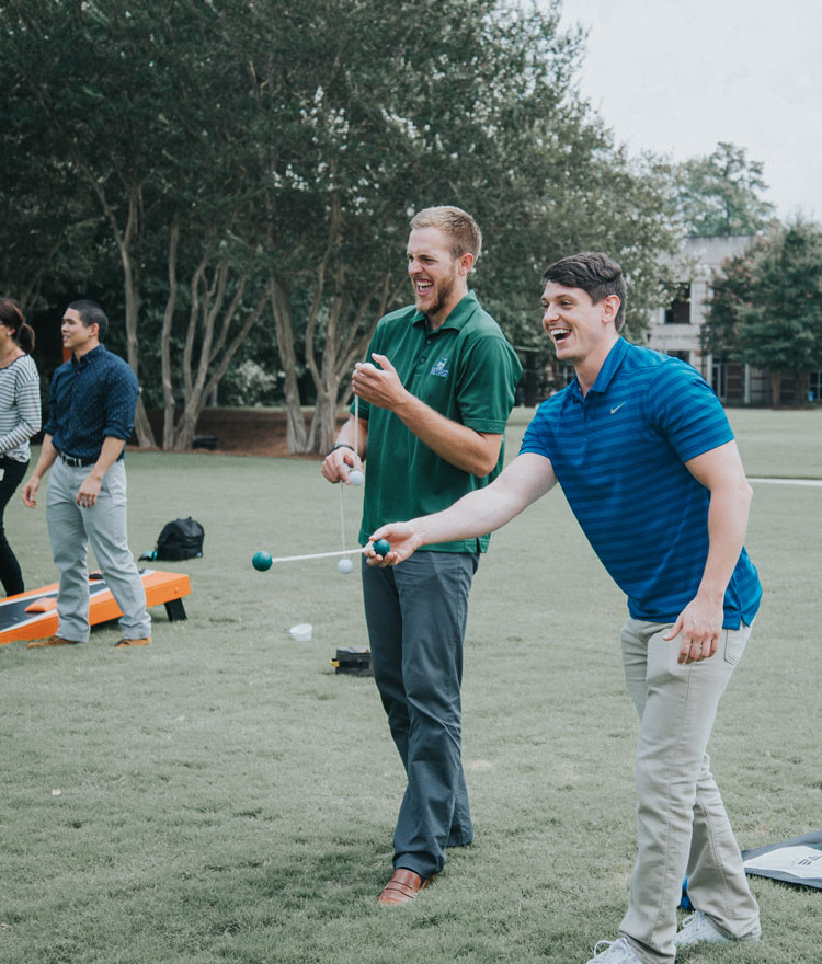 Graduate students smile while playing cornhole
