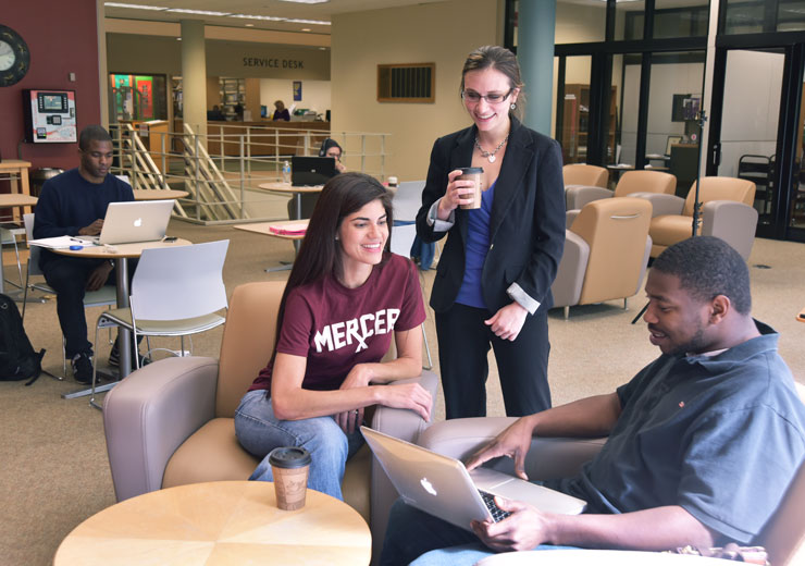 Three people talk inside the Monroe F. Swilley Jr. Library in Atlanta.