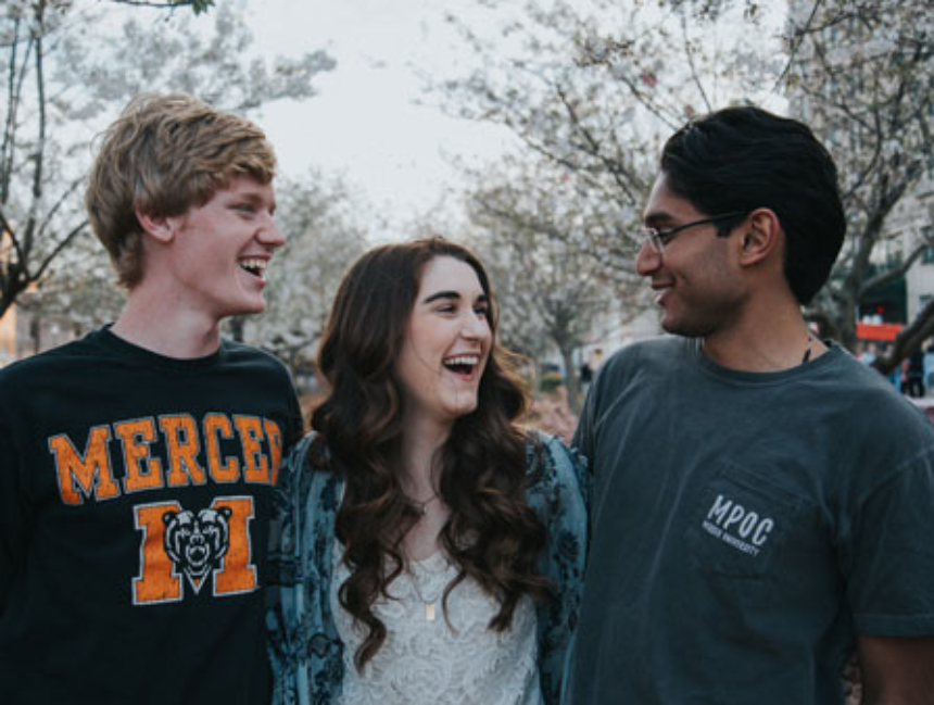 Three students hugging and smiling in downtown Macon