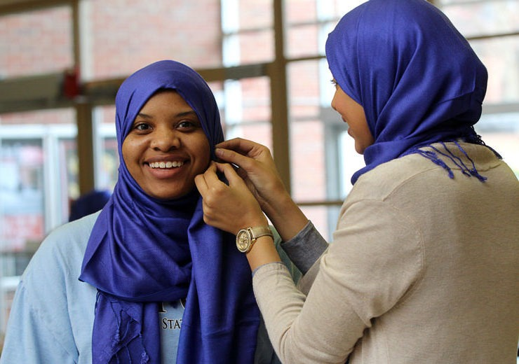 One student pins a hijab on another for World Hijab Day