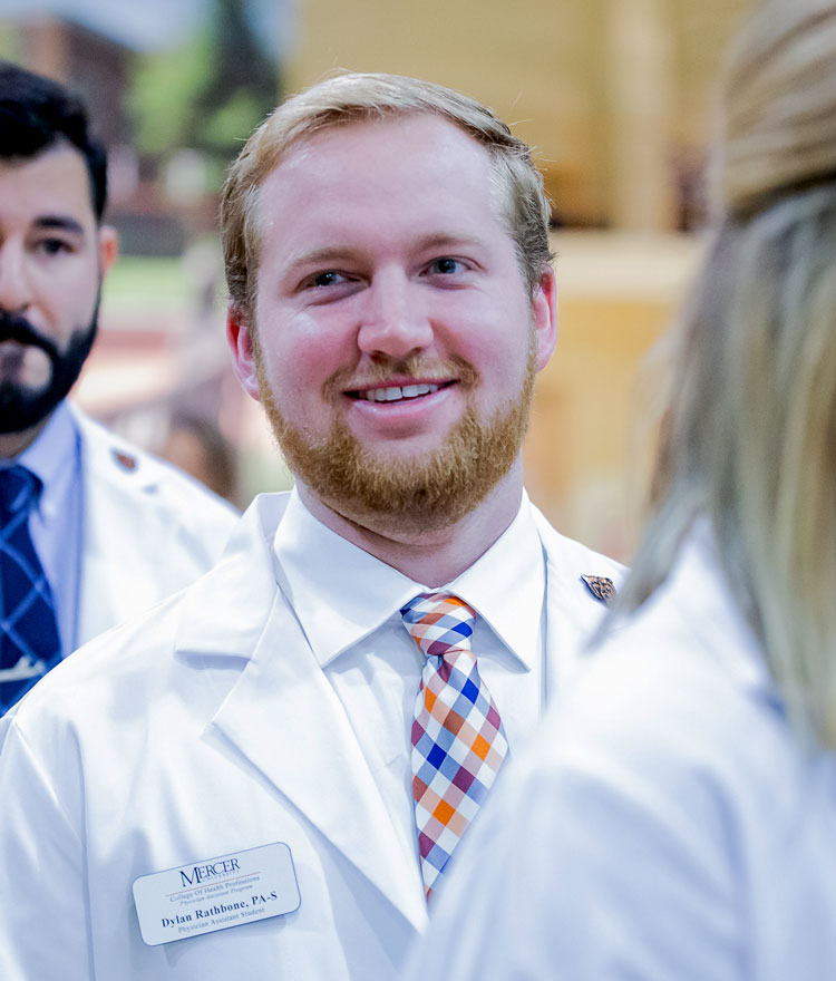 Graduate student smiles in white coat