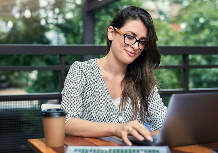 Aduly student with glasses typing on laptop