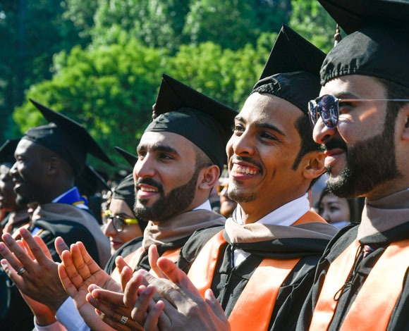 Three students smile at outdoor commencement ceremony