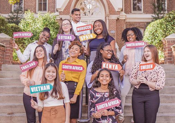 Students posing with signs of the countries they are studying abroad in this summer