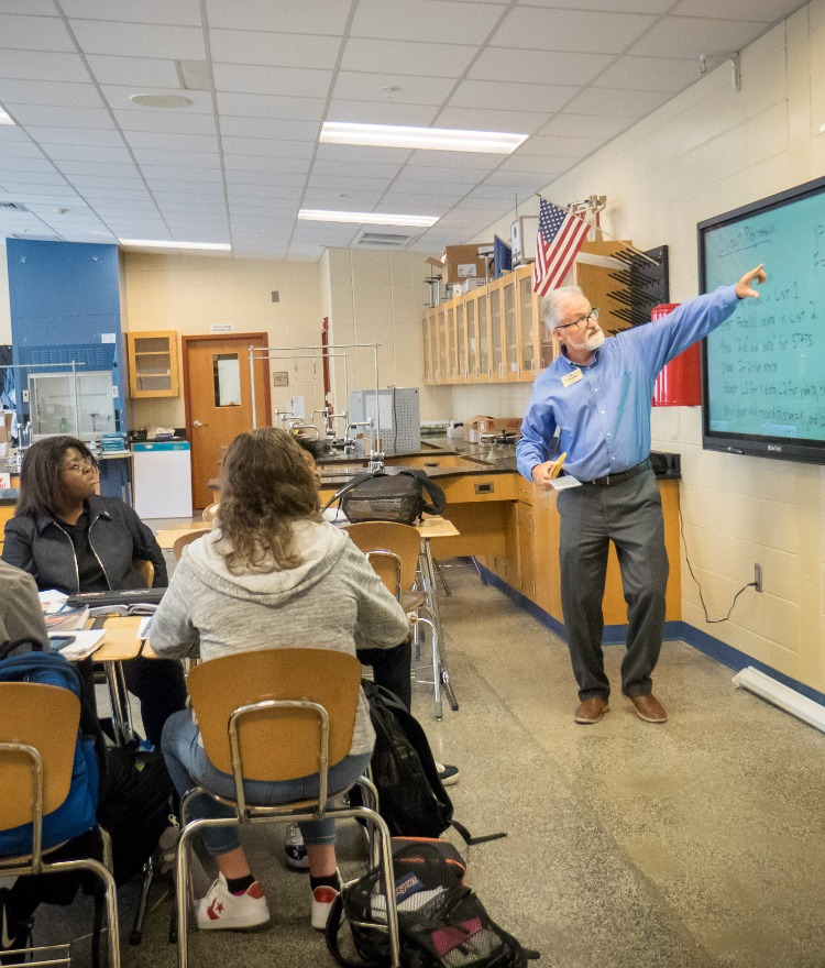 A teacher points at the board in a high school physics class.