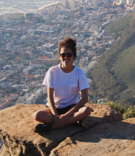 Alyssa Fortner sits on top of a mountain overlooking a city