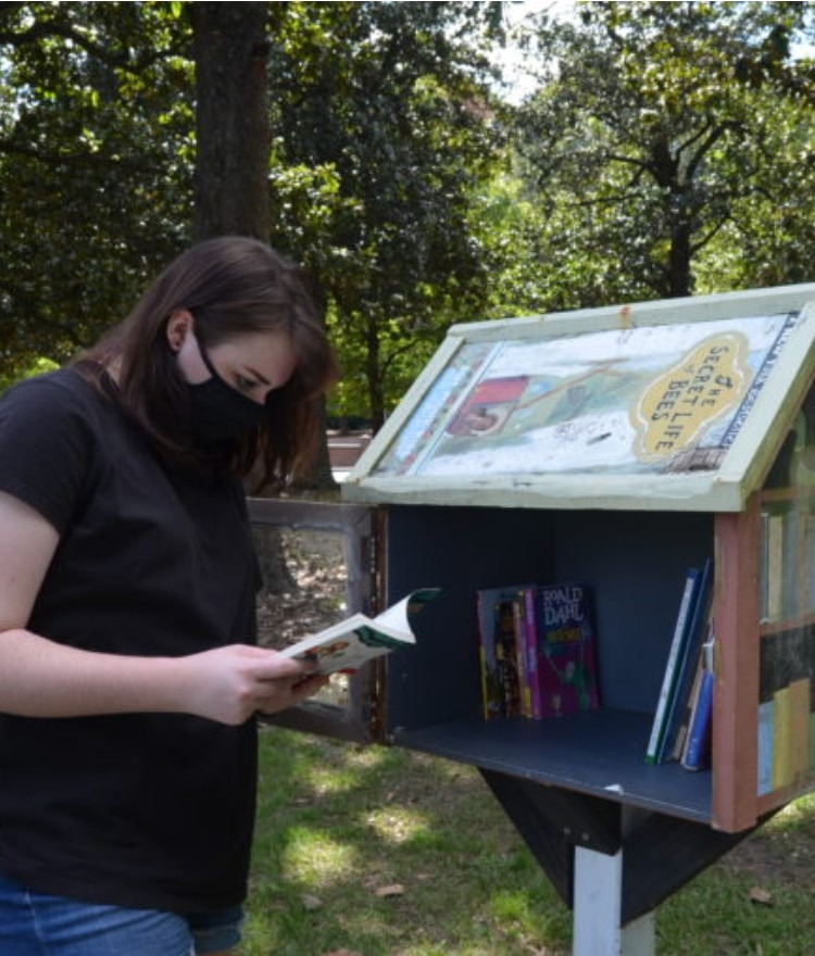 Students check a little free library box