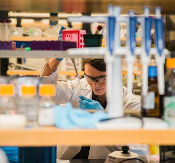 A mercer student mixes chemicals in a lab