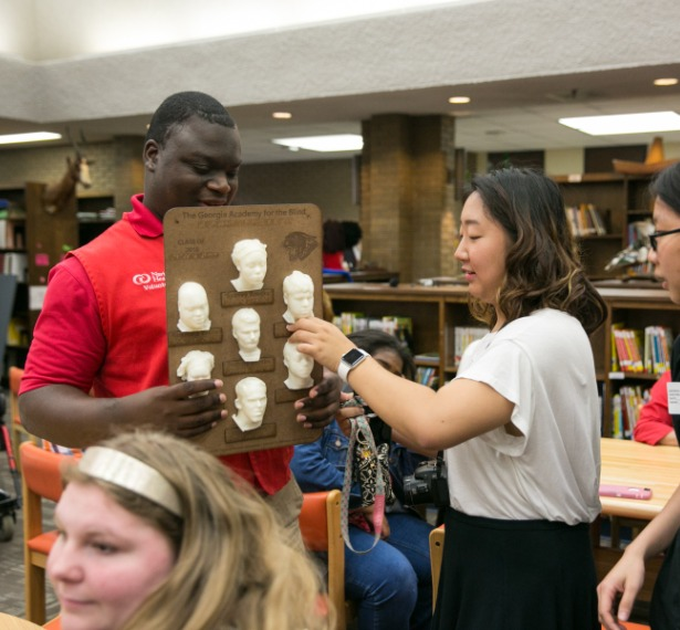 a mercer student presents a 3D yearbook to a student at the georgia academy for the blind