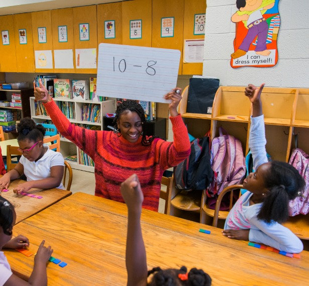 a student, surrounded by young kids, holds up a piece of paper with 10 minus 8 written on it