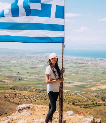 Woman stands on a mountain holding Greek flag