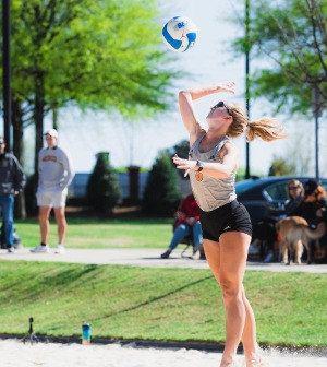 A volleyball player spikes a ball