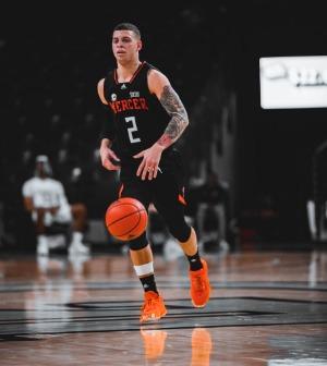 A basketball player dribbles a ball across a court