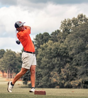 A golf player swings his club