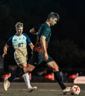 A soccer player dribbles the ball during a game