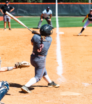 A softball player swings a bat during a game
