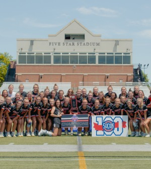 Lacrosse players pose in front of sign that says Congratulations