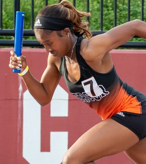 A woman holding a baton runs track