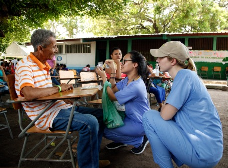two young women wearing blue scrubs kneel down to talk to a man sitting in a chair