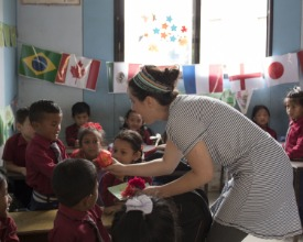 a young woman talks to a child in a class full of students
