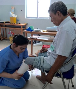 A young woman in scrubs fits a man for a prosthetic leg