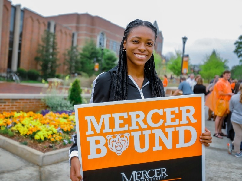 A young woman holds a sign that says Mercer Bound