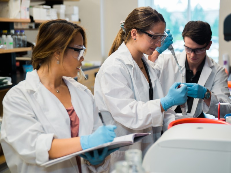 Three college students wearing white lab coats work in a lab