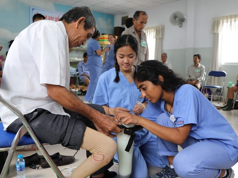 Two young women wearing scrubs fit a prosthetic leg on a man