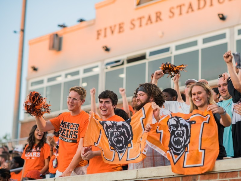 College students wearing orange hold Mercer flags and cheer in the football stands